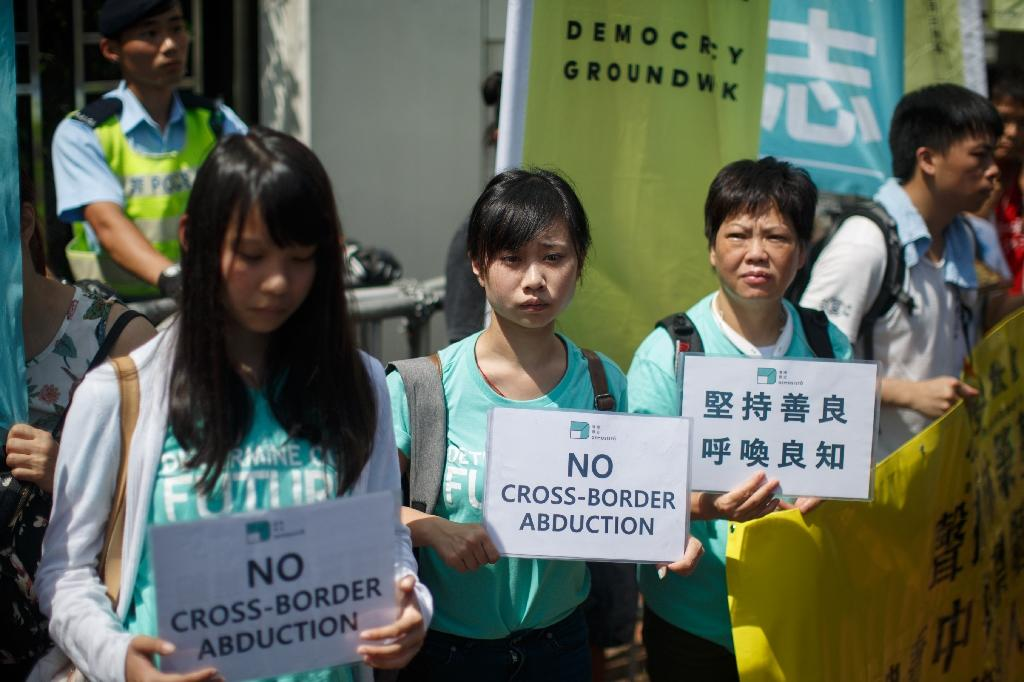 """Pro-democracy group Demosisto members hold placards reading """"No Cross-Border Abduction"""" as they protest outside the Chinese Liaison office during a protest in Hong Kong on June 17, 2016 (AFP Photo/Anthony Wallace)"""