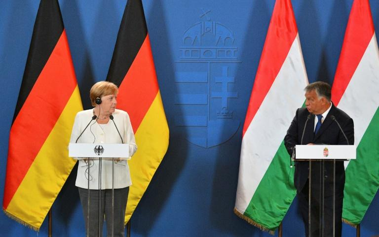 The commemoration was a rare encounter between German Chancellor Angela Merkel and Hungarian PM Viktor Orban, two of Europe's longest-running leaders (AFP Photo/Attila KISBENEDEK)