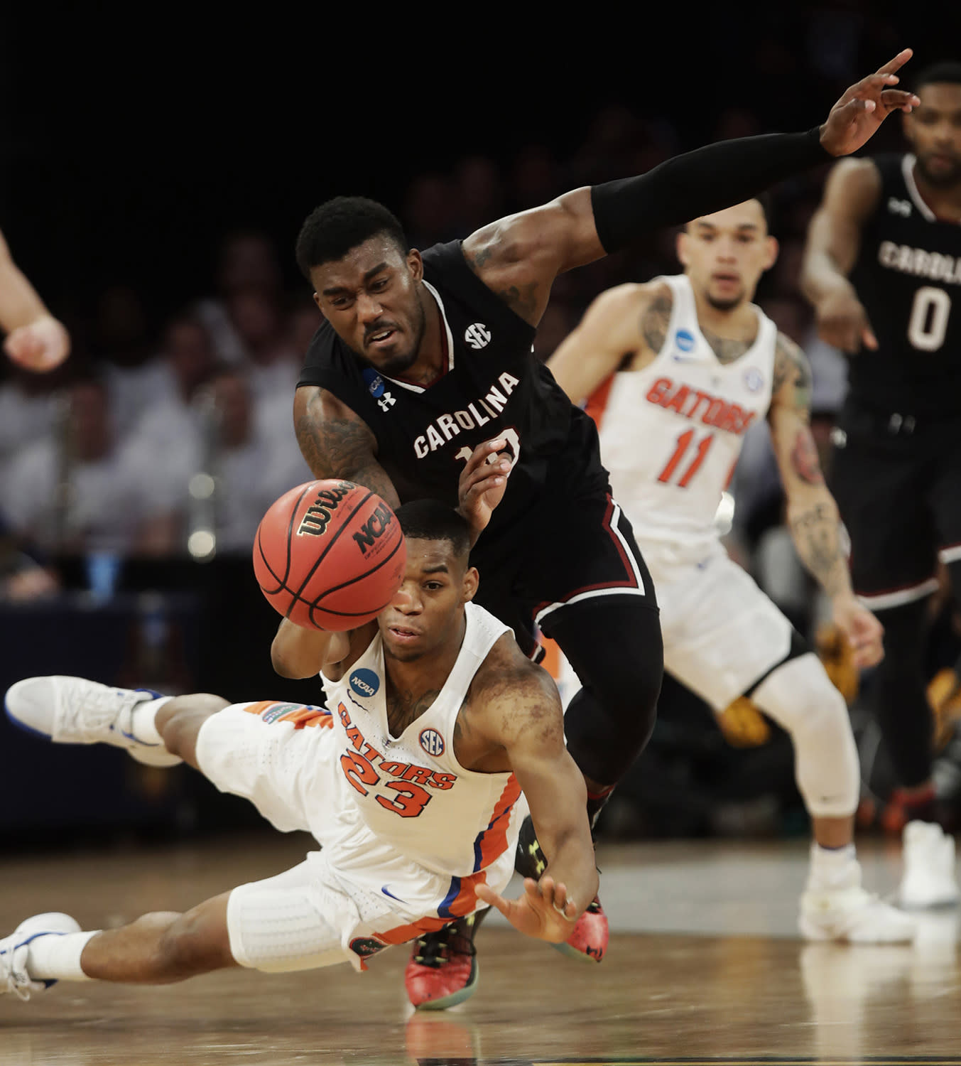 <p>Florida forward Justin Leon (23) and South Carolina guard Duane Notice (10) scramble for a loose ball during the second half of the East Regional championship game of the NCAA men's college basketball tournament, March 26, 2017, in New York. (AP Photo/Frank Franklin II) </p>
