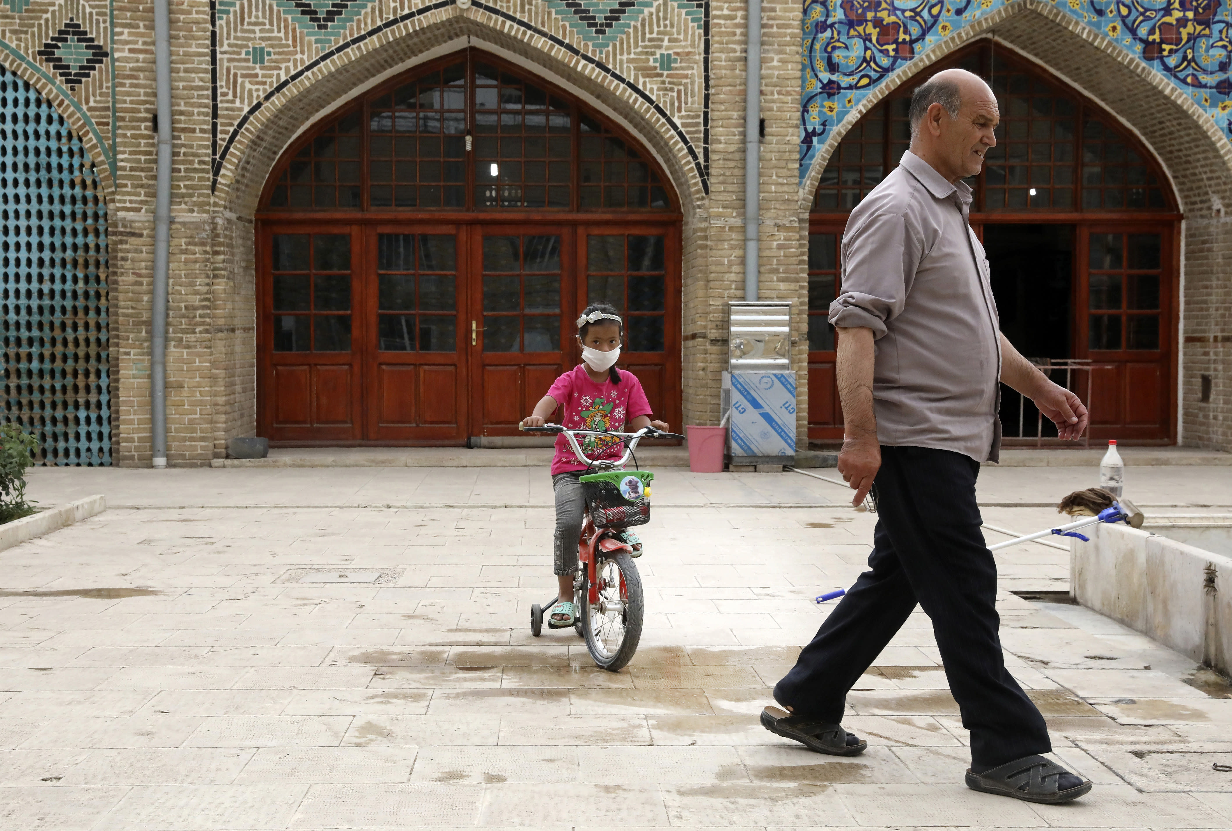 A girl wearing a protective face mask to help prevent the spread of the coronavirus rides her bicycle in the courtyard of a mosque, in the city of Zanjan, some 330 kilometers (205 miles) west of the capital Tehran, Iran, Sunday, July 5, 2020. Iran on Sunday instituted mandatory mask-wearing as fears mount over newly spiking reported deaths from the coronavirus, even as its public increasingly shrugs off the danger of the COVID-19 illness it causes. (AP Photo Vahid Salemi)