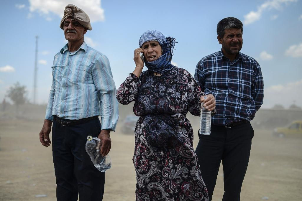 A Syrian Kurdish woman talks on the phone with her relatives in the Syrian town of Kobane during a gathering in Suruc in Turkey's Sanliurfa province near the border with Syria on June 27, 2015 (AFP Photo/Bulent Kilic)