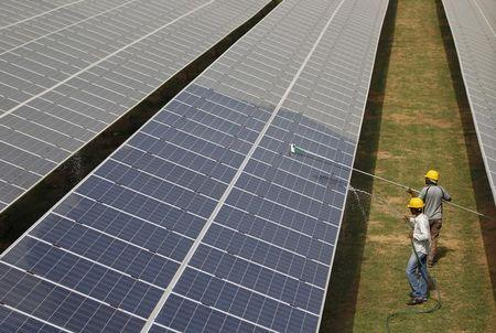 Workers clean photovoltaic panels inside a solar power plant in Gujarat