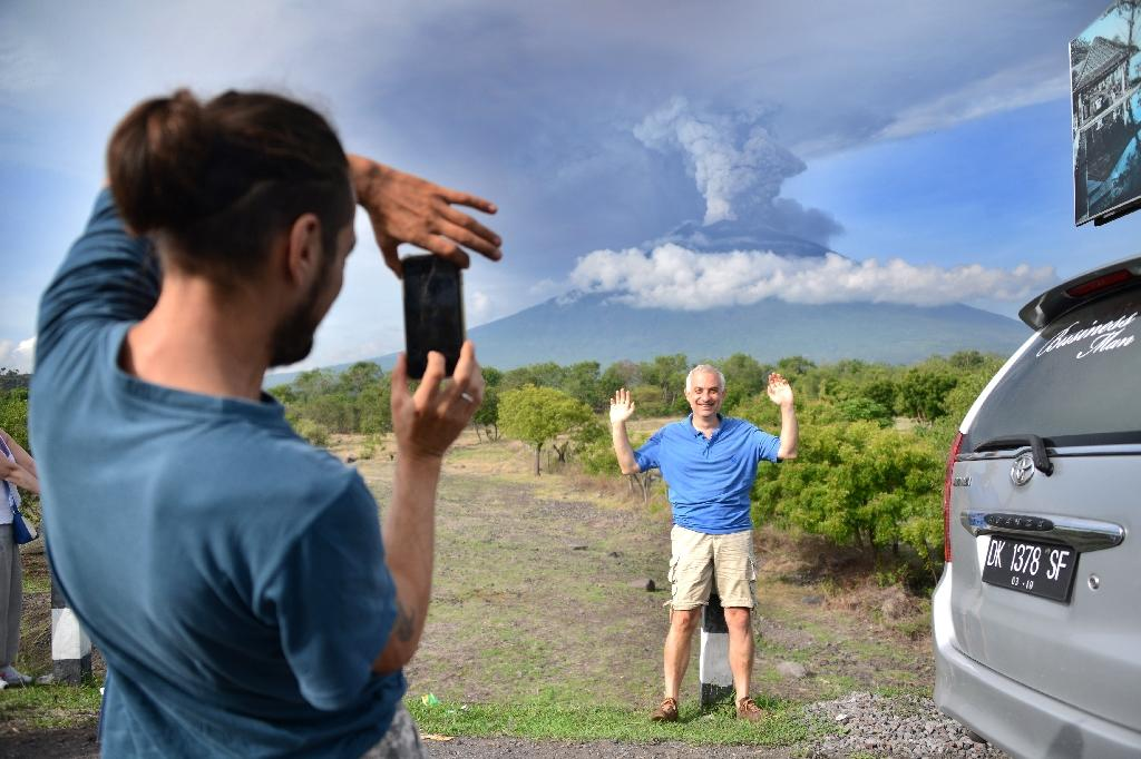 A foreign tourist takes pictures in front of Mount Agung erupting seen from Kubu sub-district in Karangasem Regency, on Indonesia's resort island of Bali on November 27, 2017 (AFP Photo/SONNY TUMBELAKA)