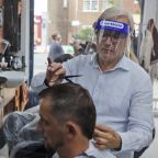 Pints poured, unkempt hairdos cut, as England eases lockdown
