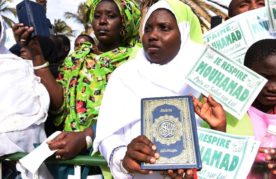 "A demonstrator holds a copy of the Koran as others display banners that translate as "" I breathe Mohammed, Peace be upon him"" in Dakar on January 24, 2015 (AFP Photo/Seyllou Diallo)"