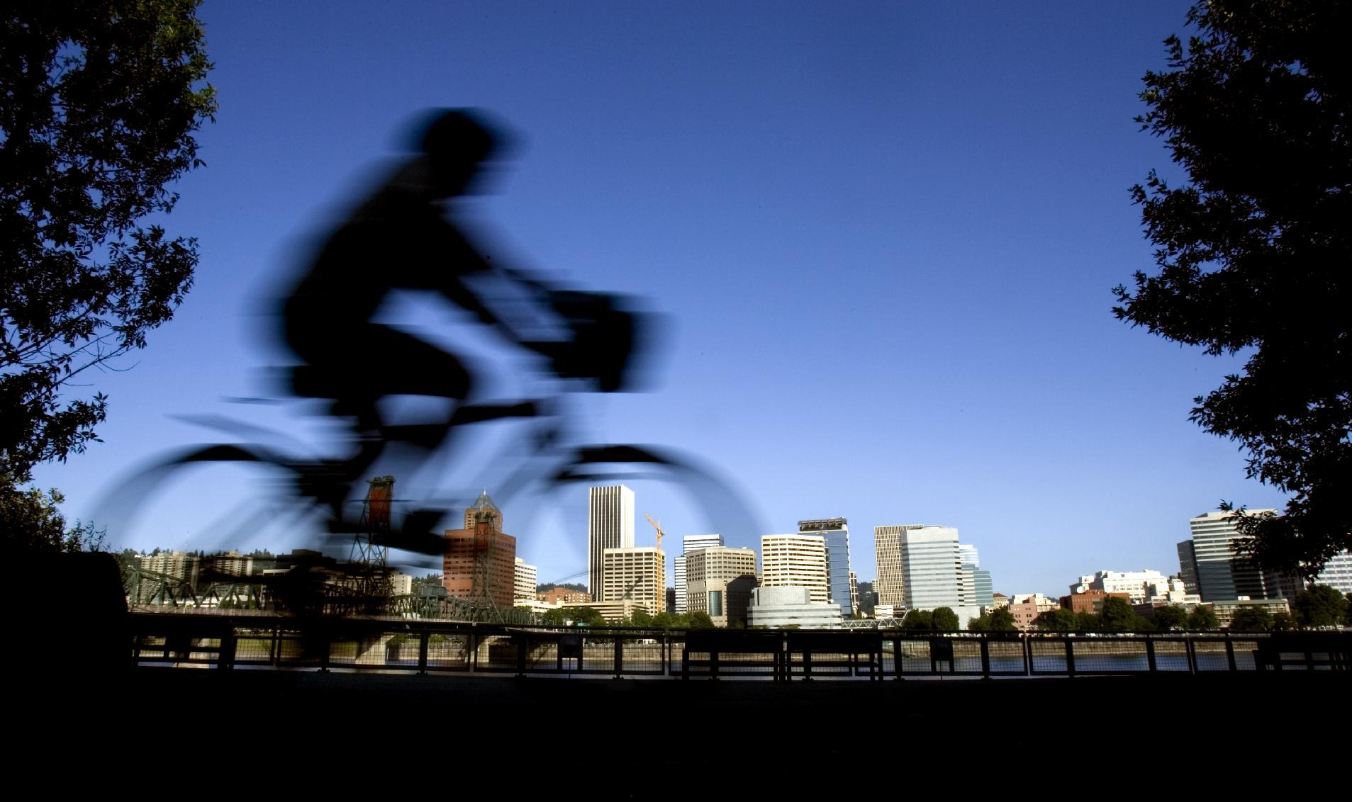 "FILE - In this July 10, 2008 file photo, a bicyclist is a blur traveling along the east bank of the Willamette River as the downtown skyline is bathed in early morning sunlight in Portland, Ore. A famous quip by Fred Armisen on the television show ""Portlandia"" led Portland State University researchers to investigate the reality behind the comment. The quirky IFC network series pokes fun at the Oregon city's many eccentricities. (AP Photo/Don Ryan, File)"