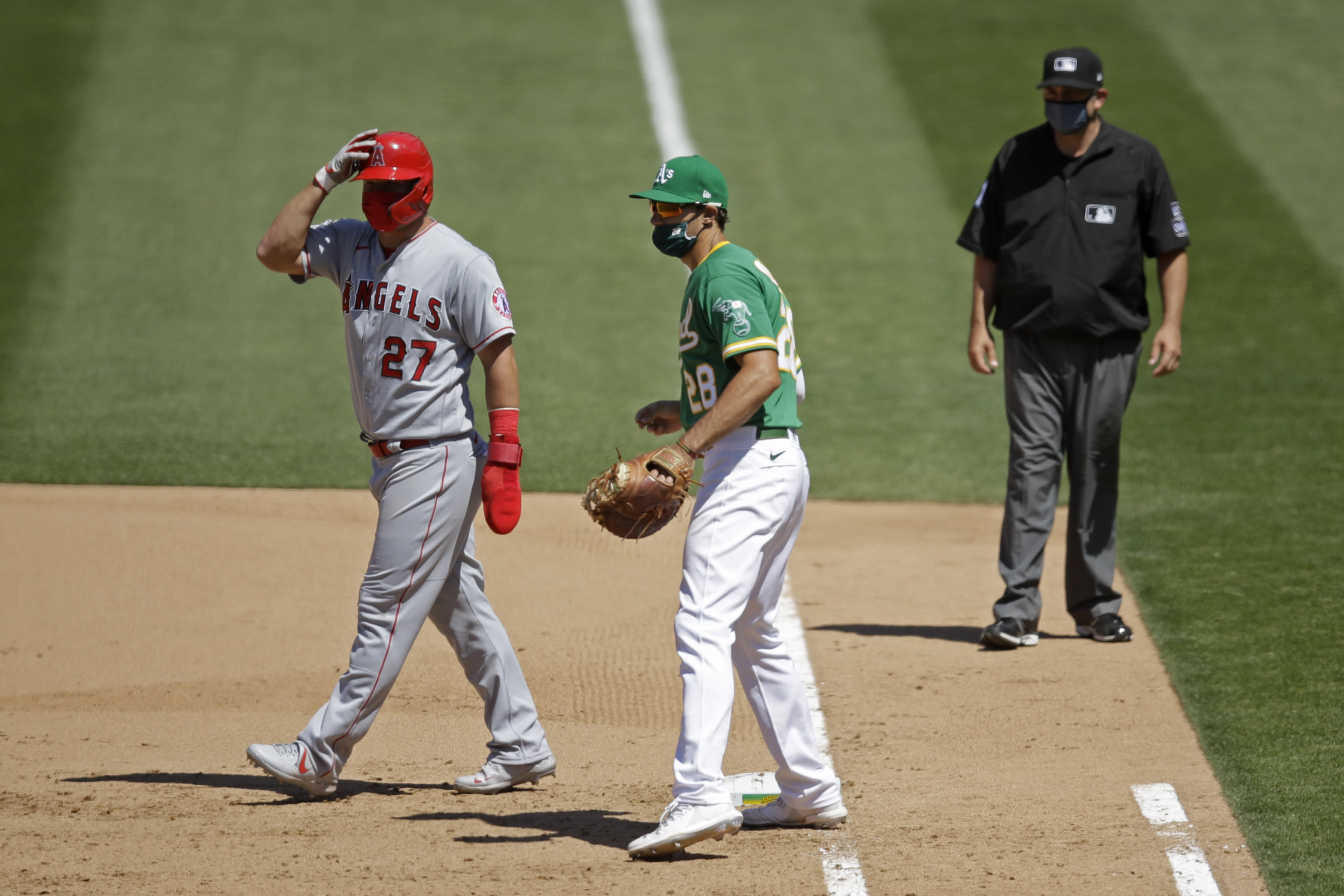 Oakland Athletics' Matt Olson (28) wears a mask as Los Angeles Angels' Mike Trout, left, also wears one while taking a lead off first base during the eighth inning of a baseball game Monday, July 27, 2020, in Oakland, Calif. (AP Photo/Ben Margot)