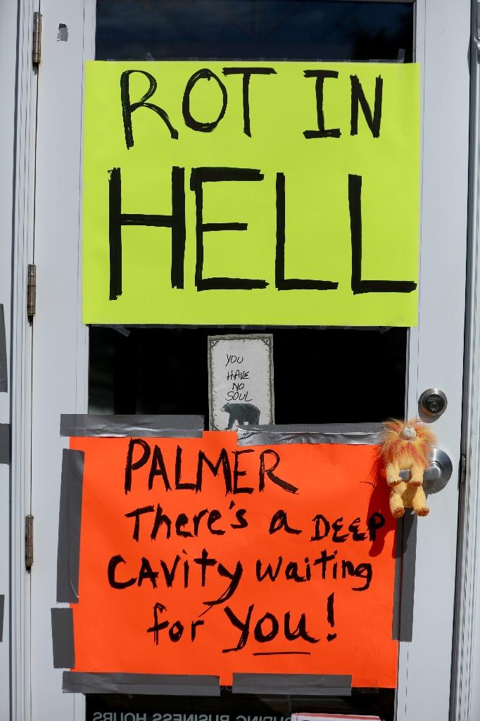 Protesters place signs on the doors of Dr. Walter Palmer's River Bluff Dental Clinic to call attention to the alleged poaching of Cecil the lion on July 29, 2015 in Bloomington, Minnesota (AFP Photo/Adam Bettcher)
