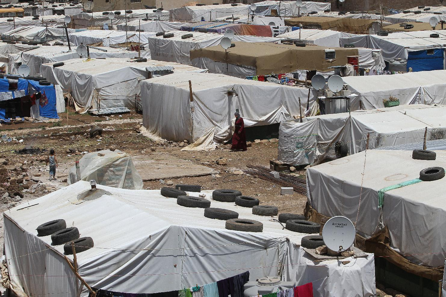 A Syrian refugee woman walks in a makeshift refugee camp in the eastern Lebanese town of Dalhamiyah on May 30, 2014