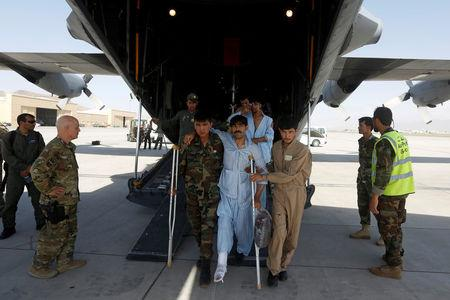 Afghan Air Force medical personnel help an injured member of the Afghan security forces to get off a C-130 military transport plane in Kabul, Afghanistan July 9, 2017. REUTERS/Omar Sobhani