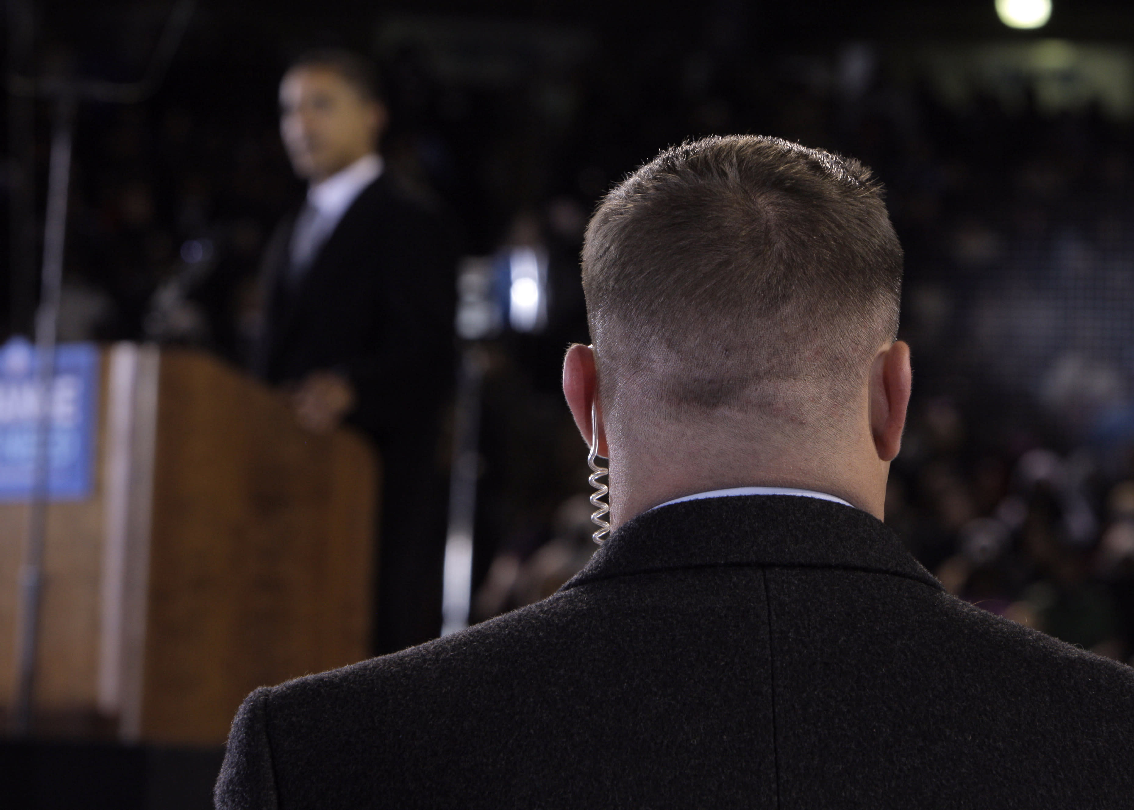 """FILE - In this Oct. 28, 2008 file photo, a Secret Service agent stands near then presidential candidate Barack Obama, background, at a rally in Norfolk, Va. Moving swiftly, the Secret Service forced out three agents Wednesday, April 18, 2012 in a prostitution scandal that has embarrassed President Obama. A senior congressman welcomed the move to hold people responsible for the tawdry episode but warned """"it's not over."""" (AP Photo/Jae C. Hong, File)"""
