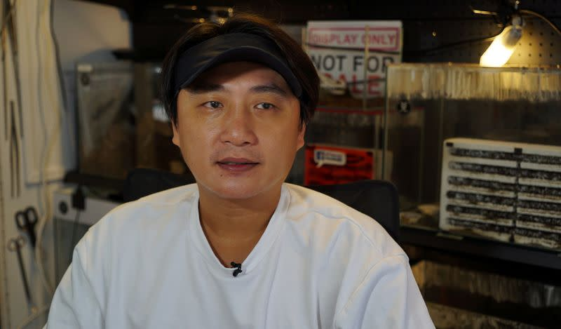 """""""Just Ants"""" owner and founder John Ye sits outside his shop during an interview with Reuters in Singapore"""