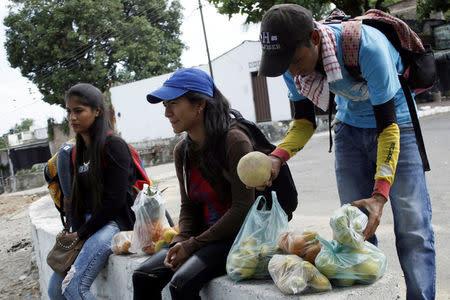 Marlon Carrillo (R) organizes the fruits bought in Venezuela as he waits for customers in Cucuta, Colombia December 15, 2017. REUTERS/Carlos Eduardo Ramirez