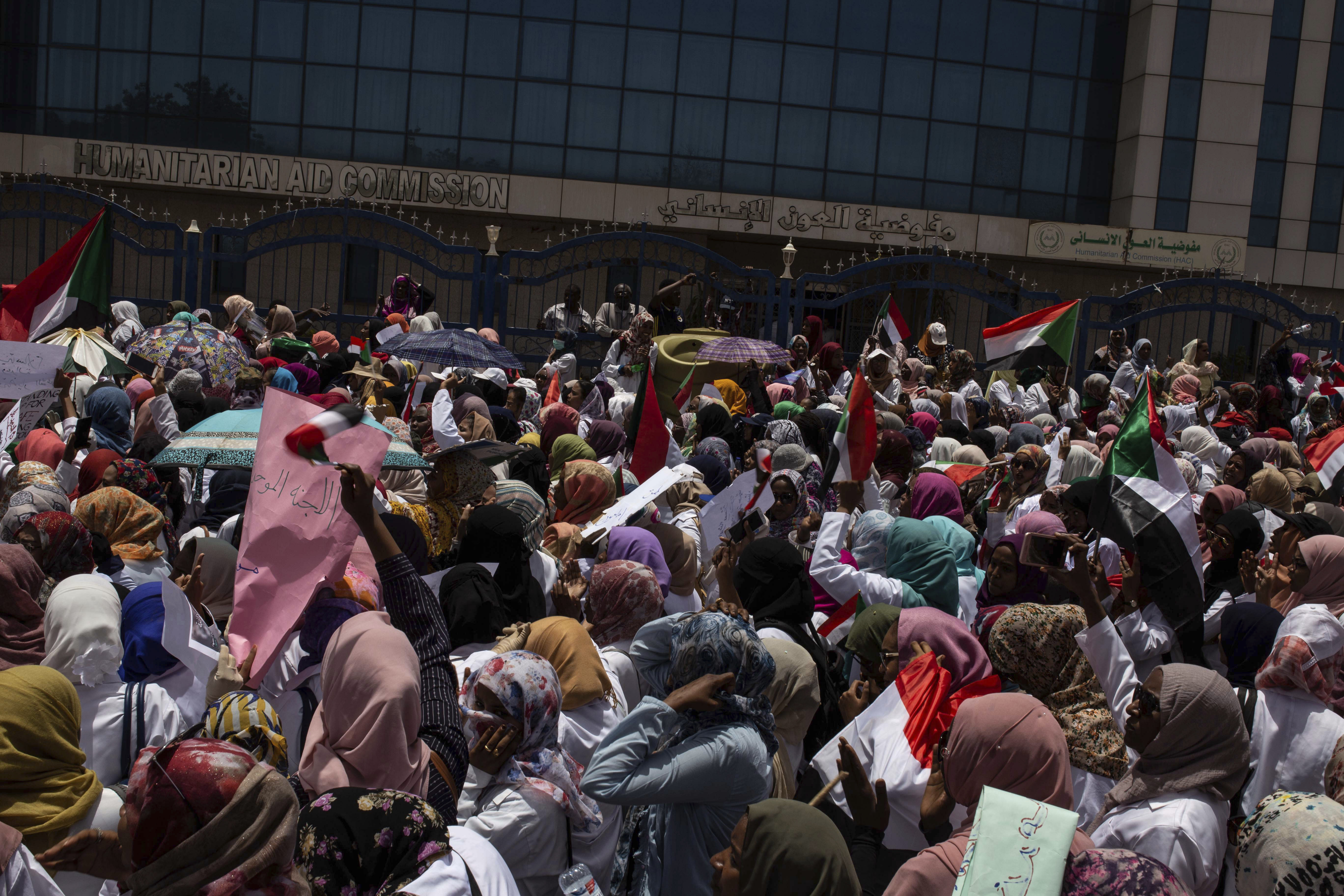 A group of protesters from the Sudanese medical profession syndicate march at the sit-in inside the Armed Forces Square, in Khartoum, Sudan, Wednesday, April 17, 2019. A Sudanese official and a former minister said the military has transferred ousted President Omar al-Bashir to the city's Kopar Prison in Khartoum. The move came after organizers of the street protests demanded the military move al-Bashir to an official prison. (AP Photos/Salih Basheer)