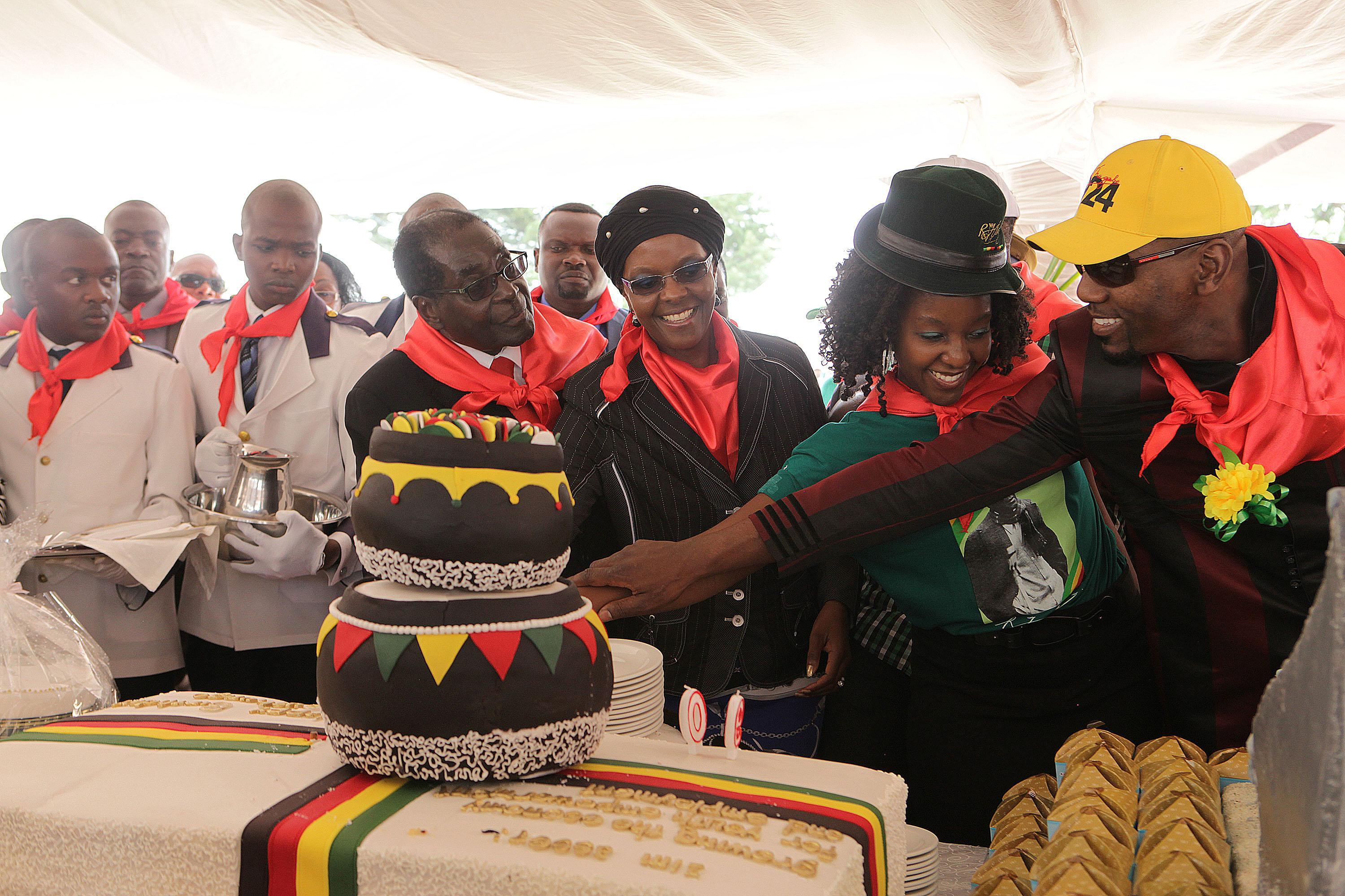 President Robert Mugabe, center left, his wife Grace, daughter Bona and her fiance Sam Chikoore cut his birthday cake during celebrations to mark his 90th Birthday in Marondera about 100 kilometres east of Harare, Sunday, February, 23, 2014. Mugabe who is Africa's oldest leader has been in power in the Southern African nation since 1980 (AP Photo/Tsvangirayi Mukwazhi)