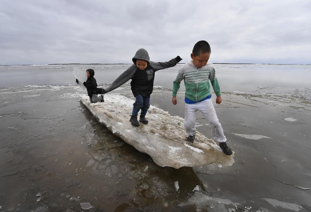 Schoolchildren play on melting ice at Yupik Eskimo village of Napakiak on the Yukon Delta in Alaska, where climate change threatens entire communities (AFP Photo/Mark RALSTON)
