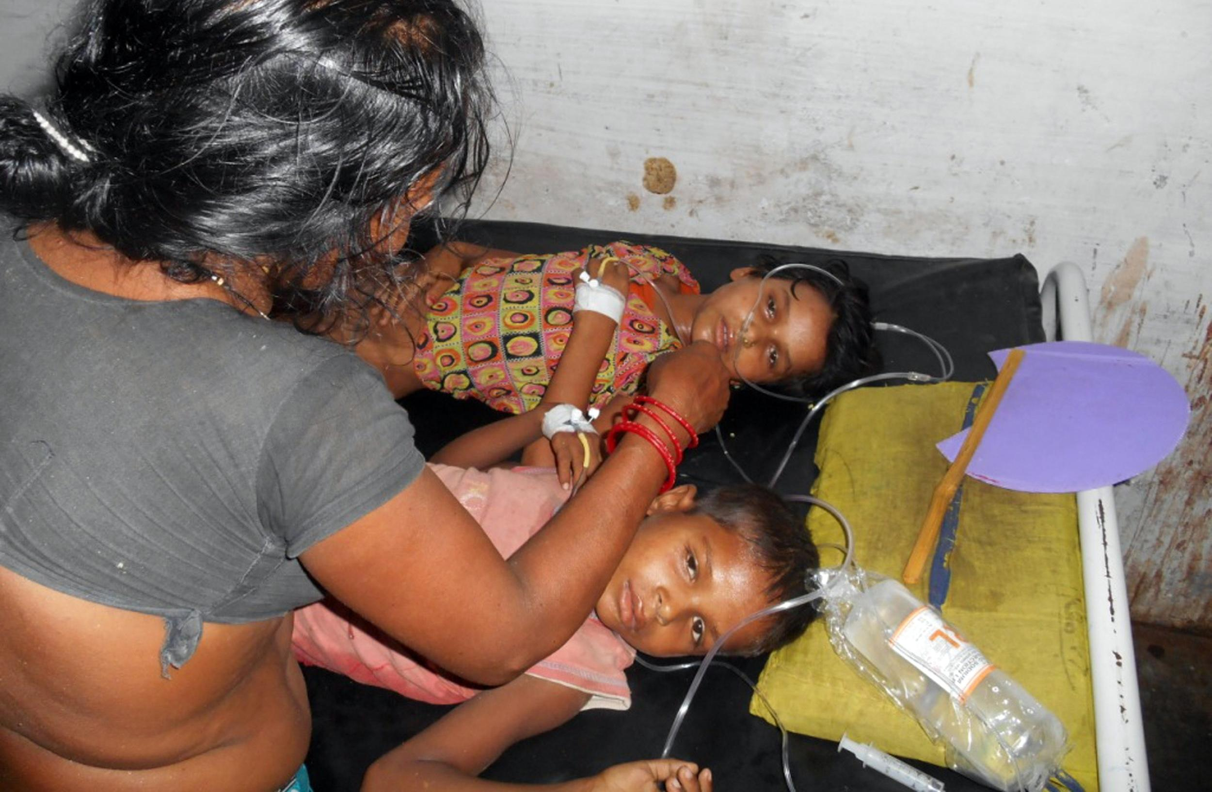 In this Tuesday, July 16, 2013 photo, schoolchildren receive treatment at a hospital after falling ill soon after eating a free meal at a primary school in Chhapra district, in the eastern Indian state of Bihar. At least 20 children have died and more are sick after eating free meals in the school, an official said Wednesday. The children are age 8 to 11. (AP Photo)