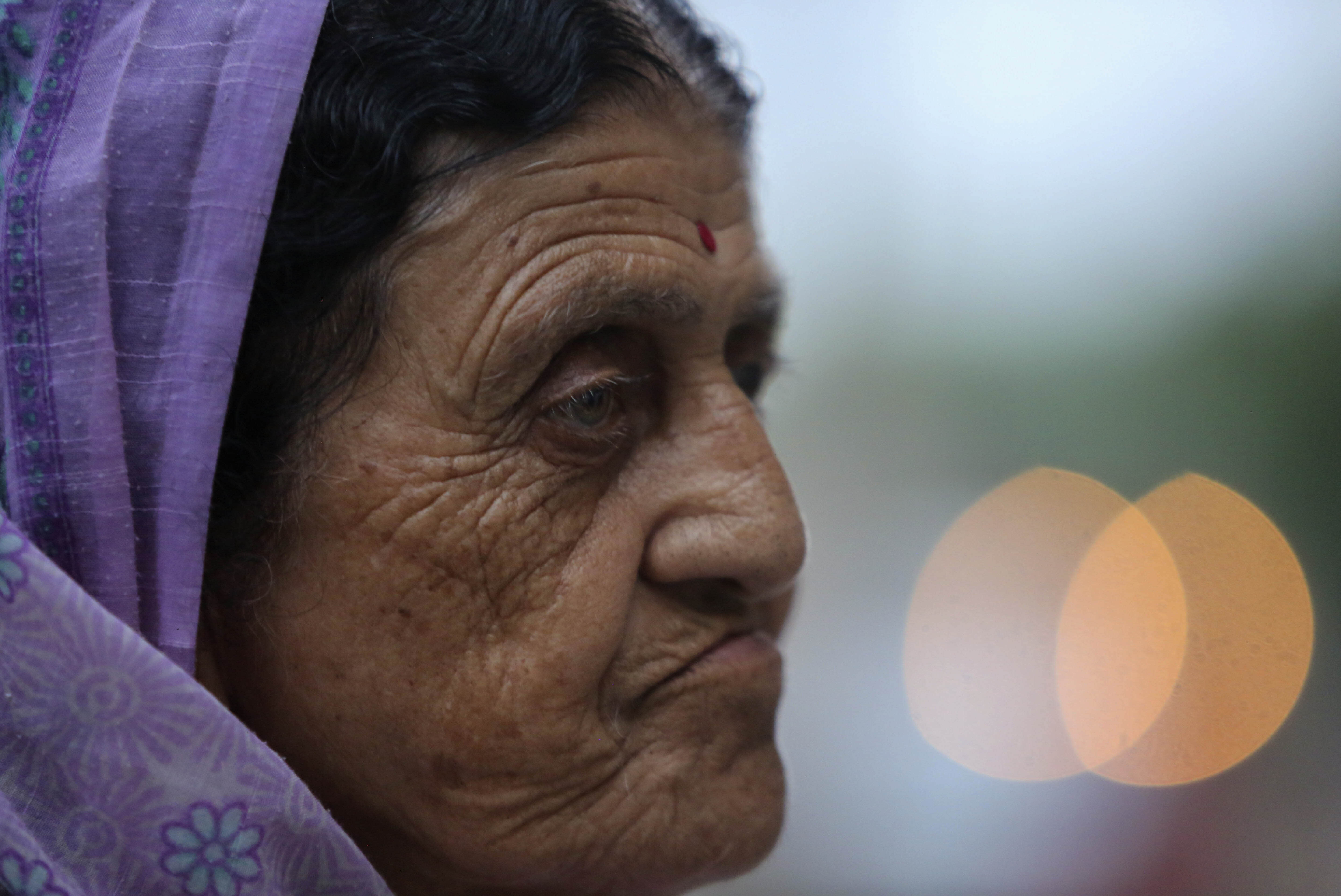 In this Aug. 29, 2019, photo, Kashmiri Hindu woman Arun Ditti, walks inside her residence at the Muthi migrant camp in Jammu, India. Tens of thousands of Kashmiri Hindus fled the restive region nearly 30 years ago, and the ghost of insurgency and their mass exodus still haunts them. They celebrated after India's Hindu nationalist-led government stripped political autonomy from its part of Muslim-majority Kashmir on Aug. 5. Kashmiri Hindus view it as a step toward justice and possible return to their homeland. But many are still wary of returning. (AP Photo/Channi Anand)
