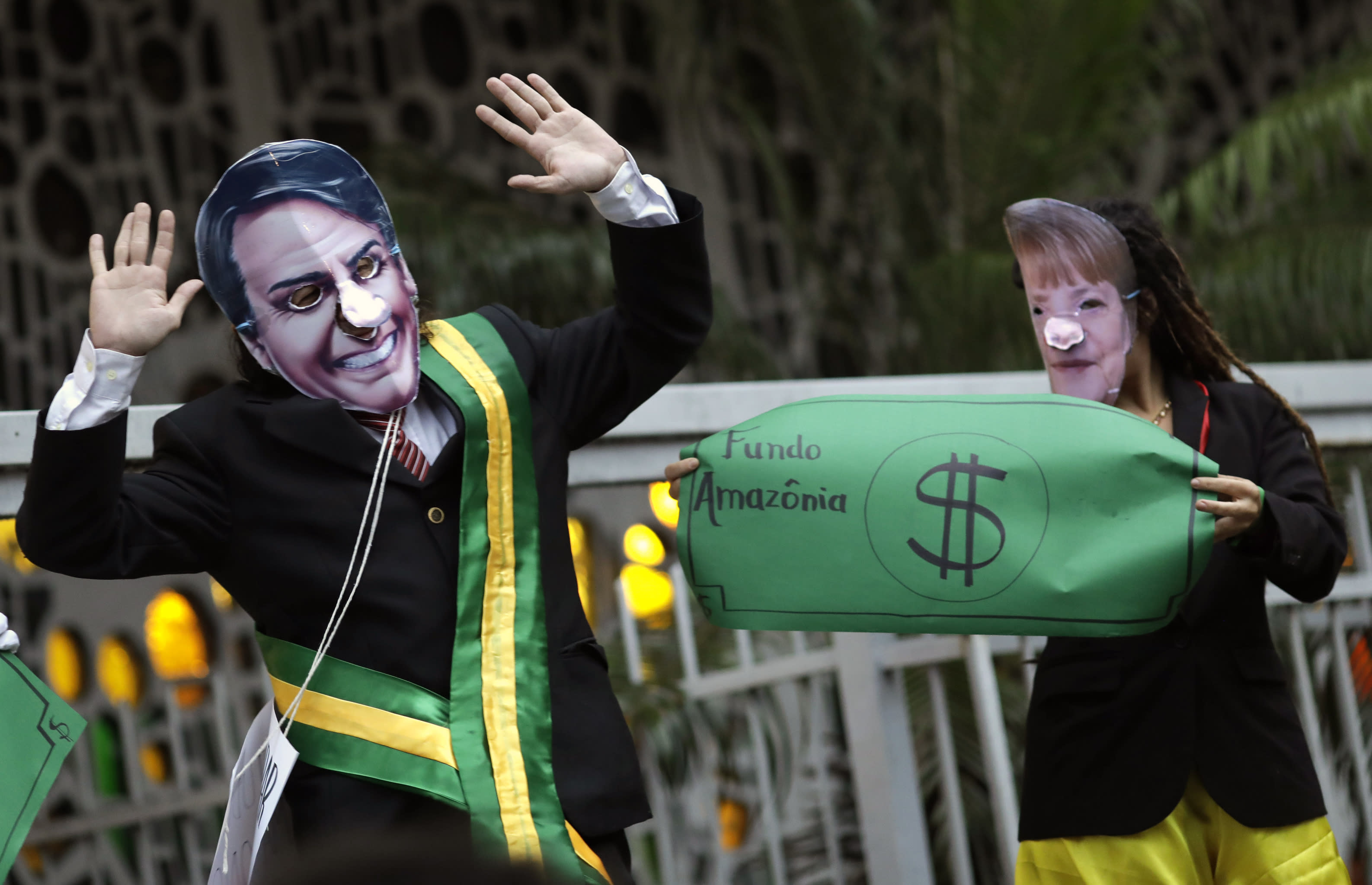 Demonstrators wear masks of Brazil's President Jair Bolsonaro, left, and Germany's Chancellor Angela Merkel during a protest in defense of the Amazon in Rio de Janeiro, Brazil, Thursday, Sept. 5, 2019. Germany has suspended a line of funding for Amazon projects. (AP Photo/Silvia Izquierdo)
