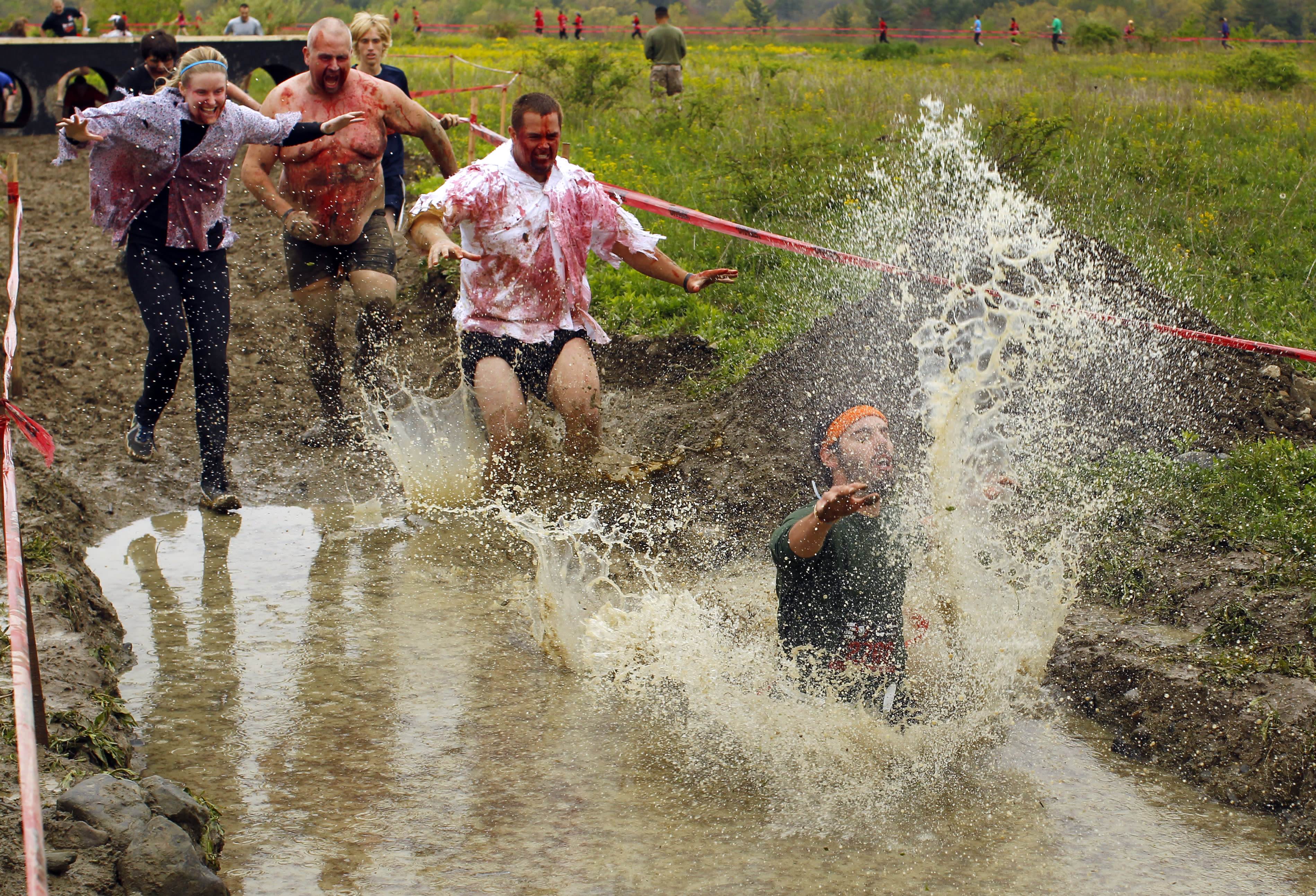 """Zombies chase a runner (R) into a pool of water on the """"Run for Your Lives"""" 5K obstacle course race in Amesbury, Massachusetts May 5, 2012. Runners face man-made and natural obstacles on the course, while being chased by zombies, who try to take """"health"""" flags off the runners belts. REUTERS/Brian Snyder"""