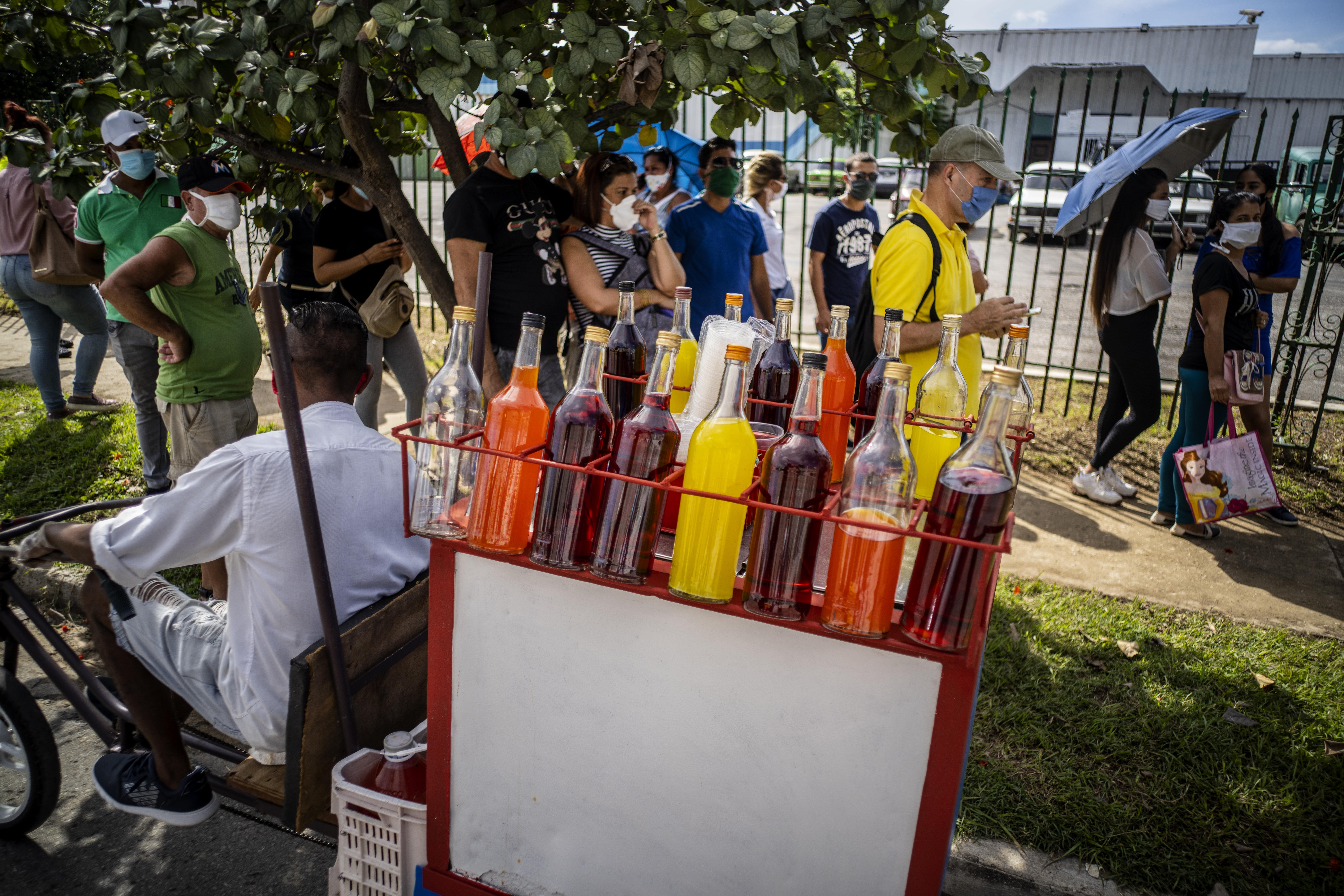 A snow cone vendor looks for customers amid a line of people, all wearing protective face masks as a precaution during the spread of the new coronavirus, waiting to enter a grocery store that accepts U.S. dollars in Havana, Cuba, Monday, July 20, 2020. Cuba has expanded the types of stores that accept dollars for payment to include food stores, as part of the government's effort to capture much needed hard currency to shore up the island's ailing economy. (AP Photo/Ramon Espinosa)
