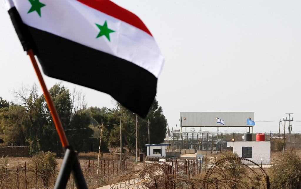 The Syrian national flag flies in front the Quneitra border crossing into the Israeli annexed-Golan Heights