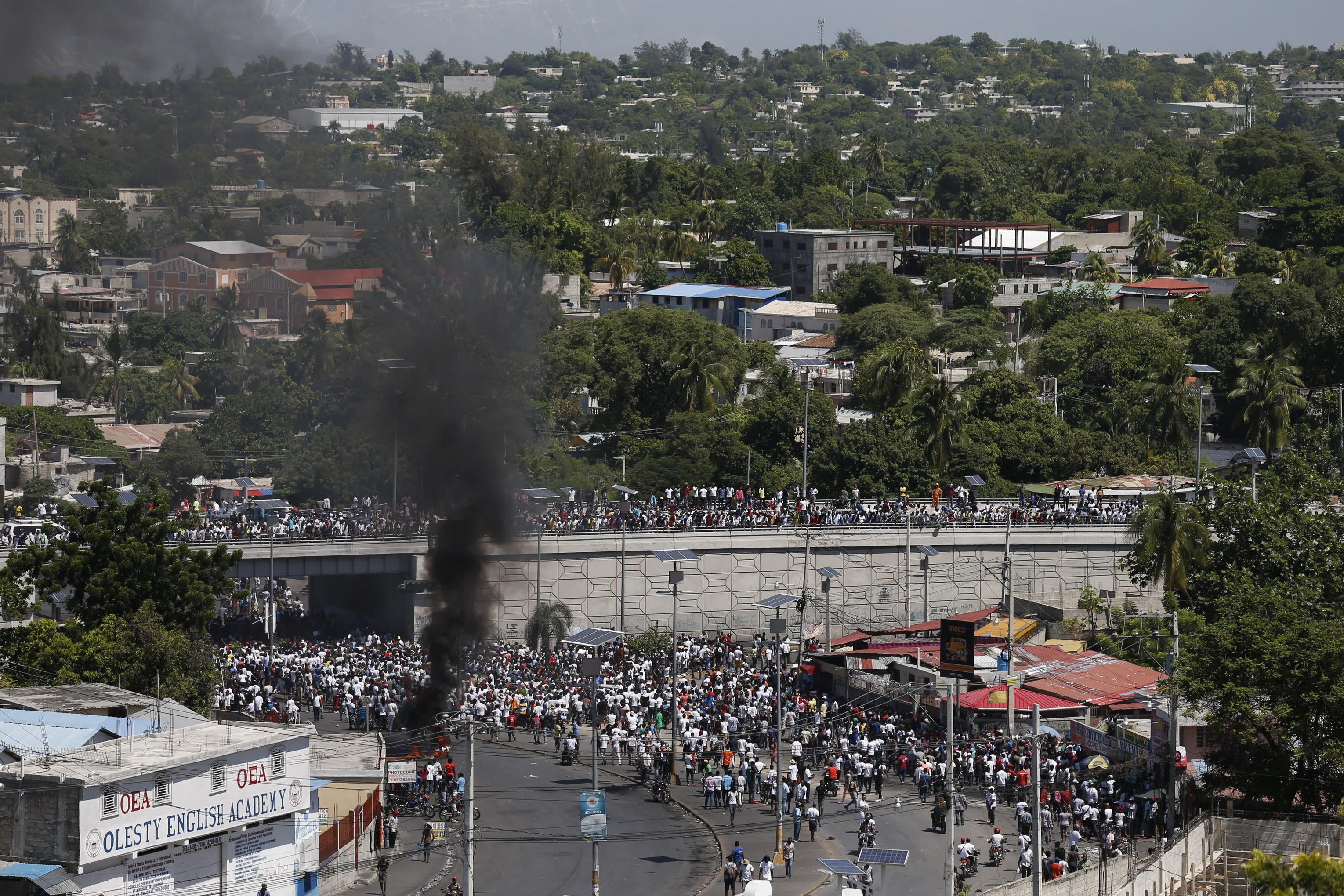 Protesters led by the art community demand the resignation of Haitian President Jovenel Moise as they march through Port-au-Prince, Haiti, some having set debris on fire, Sunday, Oct. 13, 2019. Protests have paralyzed the country for nearly a month, shuttering businesses and schools. (AP Photo/Rebecca Blackwell)