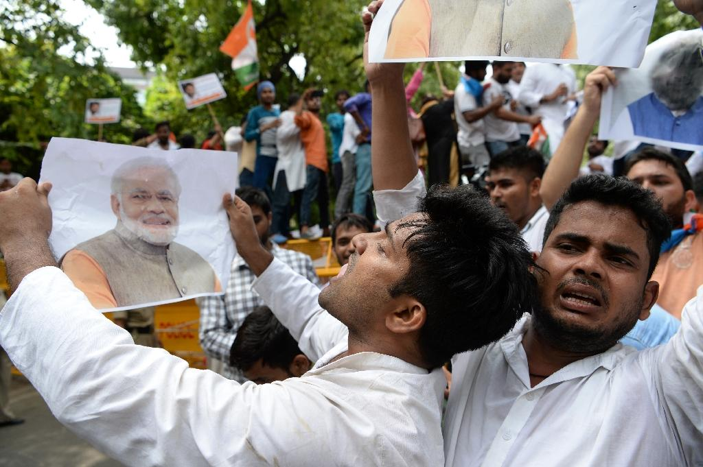 Congress Party supporters have staged angry nationwide protests, blaming supporters of Prime Minister Narendra Modi for pelting stones at the car of its leader Rahul Gandhi (AFP Photo/SAJJAD HUSSAIN)