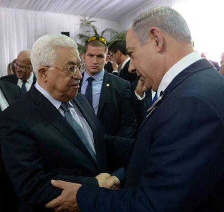 Israeli PM Netanyahu shakes hands with Palestinian President Abbas during funeral of former Israeli President Shimon Peres in Jerusalem