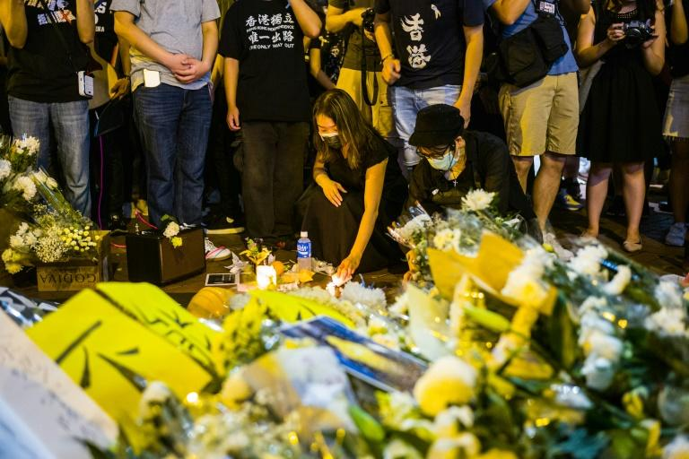 Pro-democracy activists in Hong Kong pay their respects in June 2020 to mark the one-year anniversary of the death of a man who took a fatal fall after hanging a banner against a now-withdrawn extradition bill that sparked mass protests (AFP