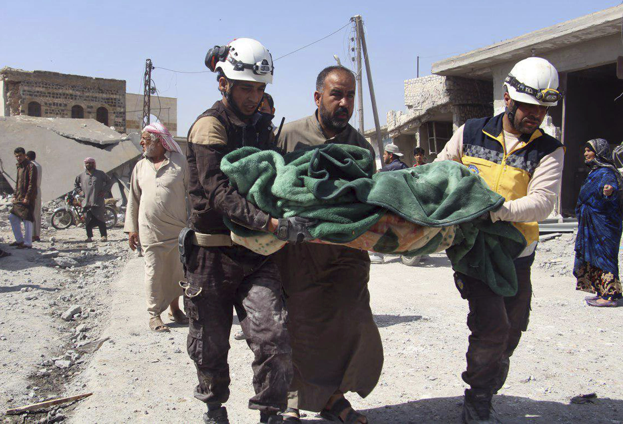 This photo provided by the Syrian Civil Defense group known as the White Helmets, shows members of the Syrian Civil Defense workers carrying a victim after a deadly airstrike hit a market killing several people in the village of Ras el-Ain, in the northwestern province of Idlib, Syria, Tuesday, May 7, 2019. Opposition activists say government forces have intensified their bombardment of rebel-held towns and villages in northwestern Syria. (Syrian Civil Defense White Helmets via AP)