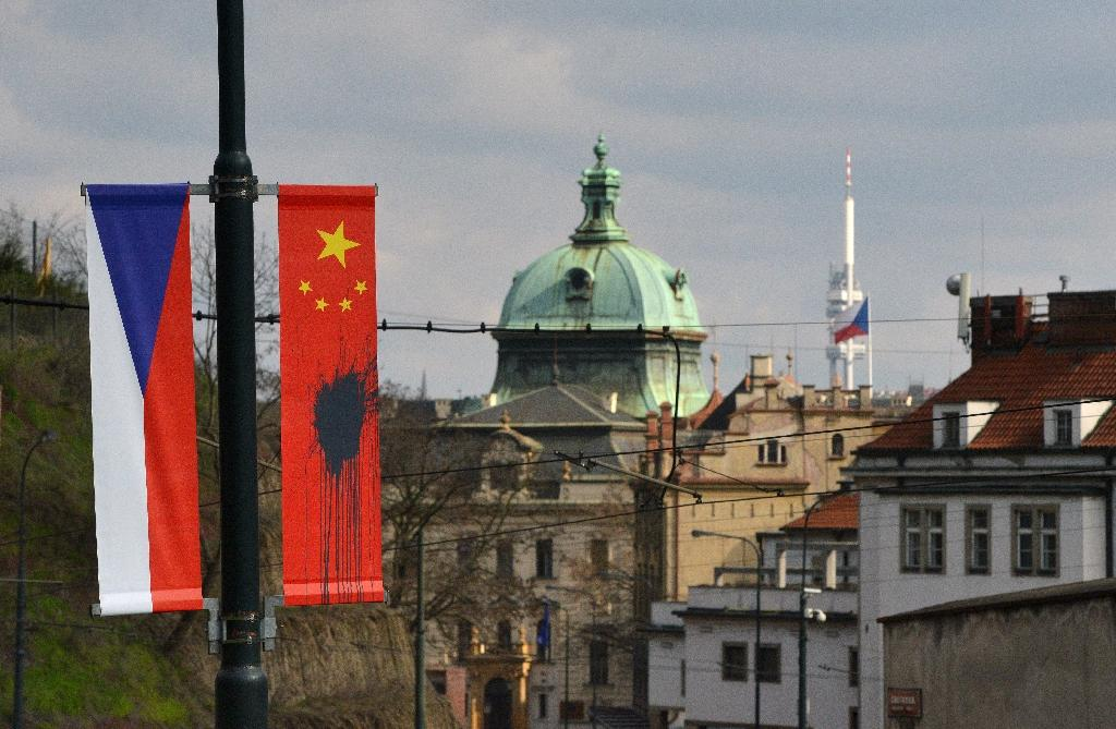 A Czech flag hangs next to a Chinese flag splattered with a black substance, in Prague on March 26, 2016 (AFP Photo/Michal Cizek)