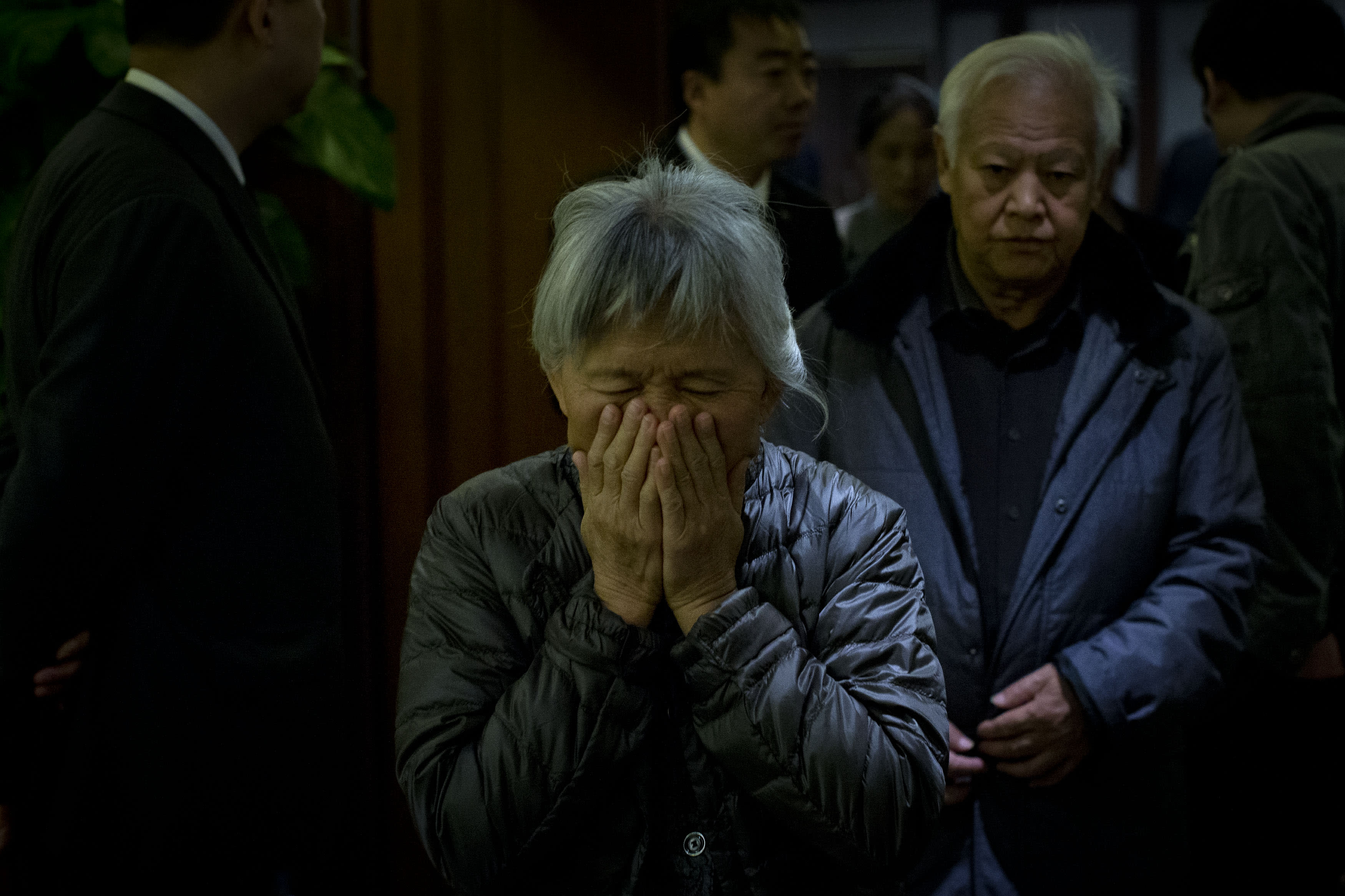 An elderly woman, one of the relatives of Chinese passengers aboard missing Malaysia Airlines Flight MH370, covers her face out of frustration as she leaves a hotel ballroom after a daily briefing meeting with managers of Malaysia Airlines in Beijing, China, Wednesday, March 19, 2014. Search crews from 26 countries are looking for Malaysia Airlines Flight 370, which vanished early March 8 with 239 people aboard en route from Kuala Lumpur to Beijing. Frustration is growing among relatives of those on the plane at the lack of progress in the search. (AP Photo/Alexander F. Yuan)