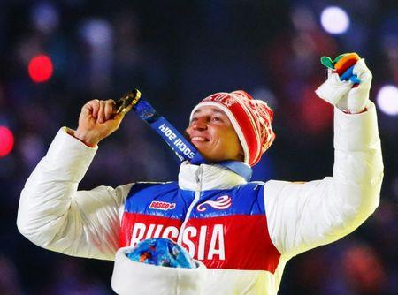 Russian gold medalist Legkov celebrates as he receives his medal during closing ceremony for Sochi 2014 Winter Olympics