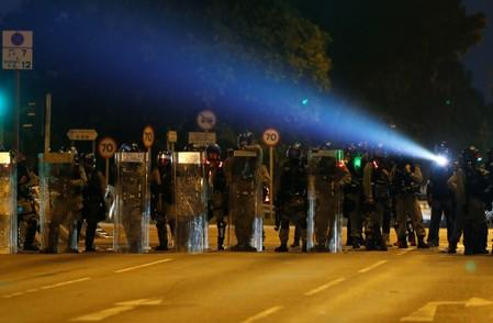 Riot police officers block the street during an anti-government protest in Tai Po district, in Hong Kong