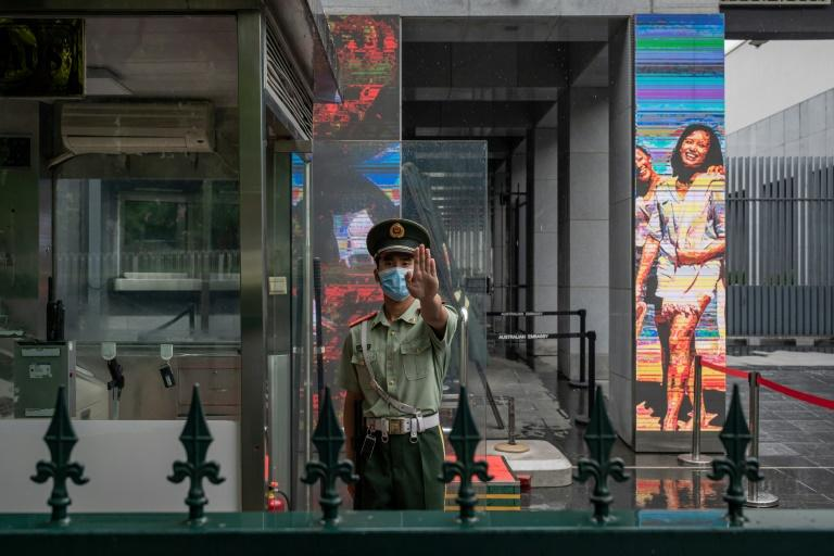 A Chinese paramilitary police officer stands at the entrance of the Australian embassy in Beijing in July 2020 amid high tensions (AFP Photo/NICOLAS ASFOURI)