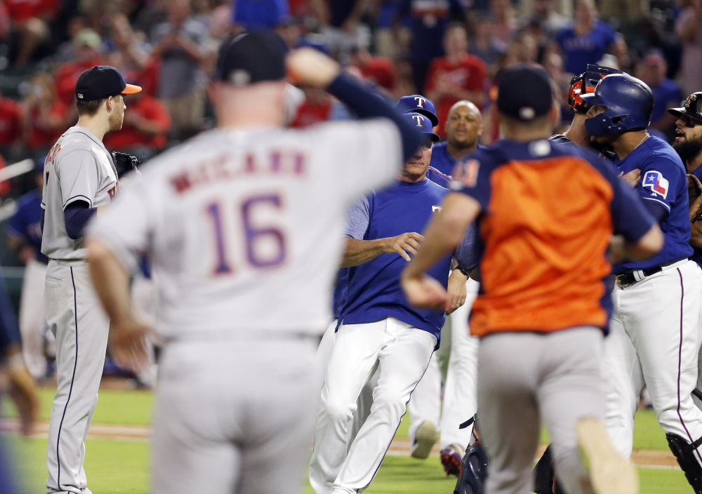 Carlos Gomez (far right) goes after Astros pitcher Collin McHugh during Monday's game. (Getty Images)