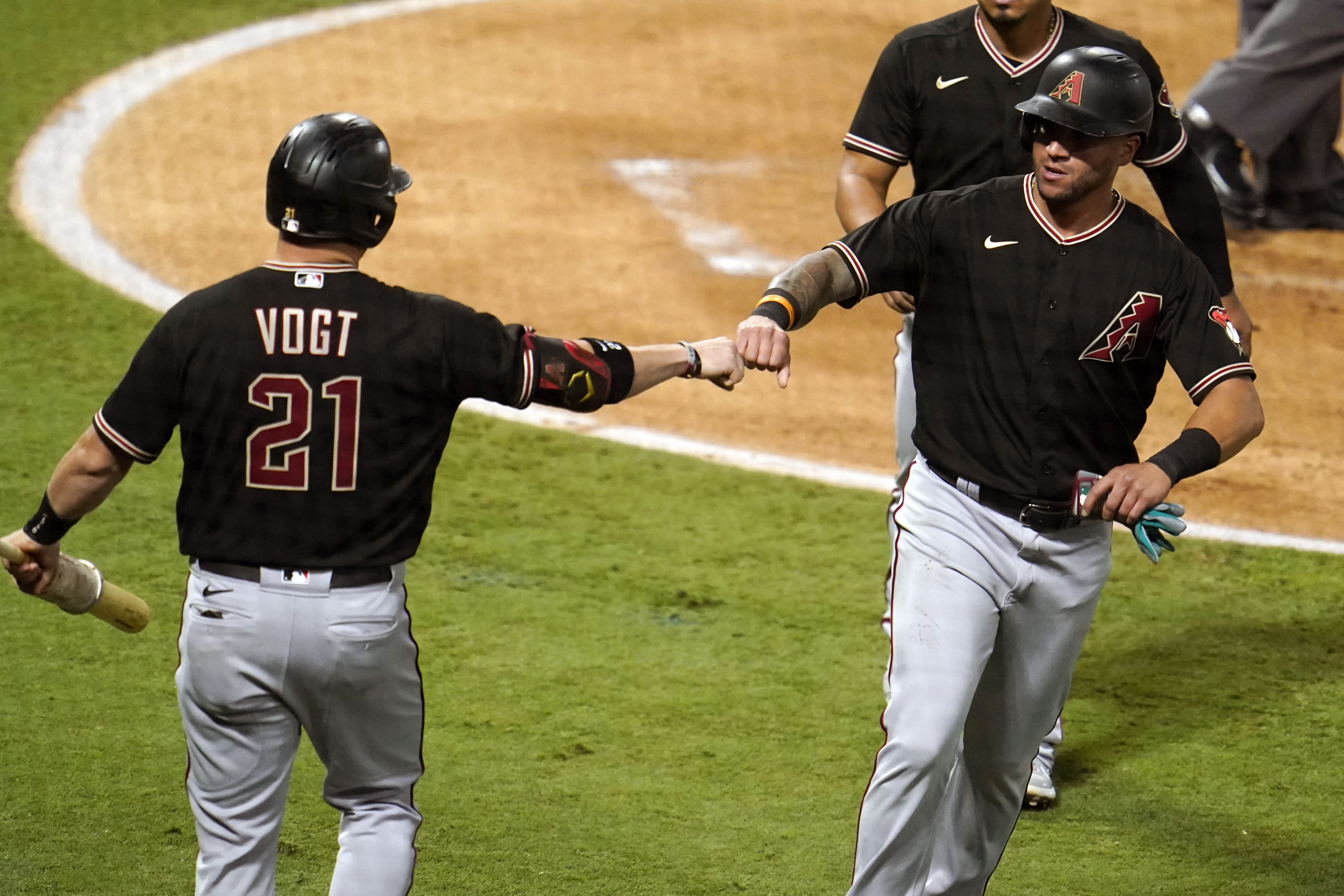 Arizona Diamondbacks' David Peralta, right, bumps fists with Stephen Vogt after Peralta score on a single from Nick Ahmed during the second inning of a baseball game against the Los Angeles Angels Wednesday, Sept. 16, 2020, in Anaheim, Calif. (AP Photo/Marcio Jose Sanchez)
