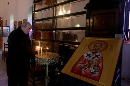 A man lights candles at Saint Nikolla church near where fallen Greek World War Two soldiers are buried, in Kelcyra, Albania January 24, 2018. Picture taken January 24, 2018. REUTERS/Florion Goga