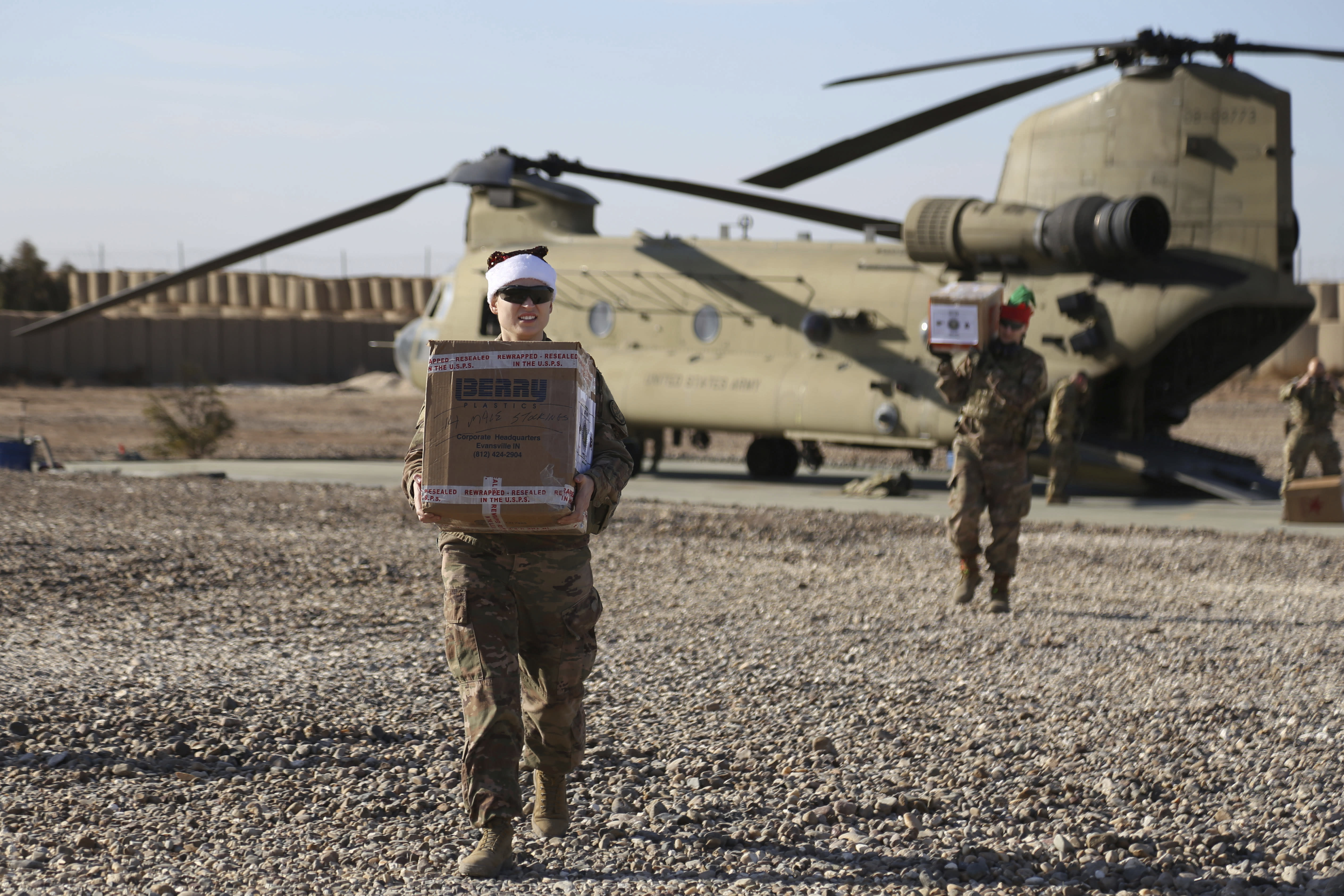 In this Tuesday, Dec. 24, 2019, photo, U.S. service members deliver Christmas gifts to their comrades on a base near the al-Omar oilfield in eastern Syria. It's an operation is called Holiday Express - in addition to delivering presents, the U.S.-led coalition forces brought a U.S. military band to play Christmas carols and music to several bases in eastern Syria. (AP Photo/Farid Abdul-Wahid)