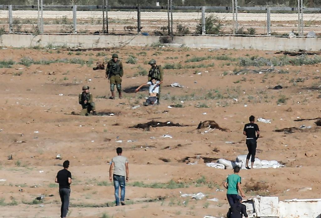 Israeli soldiers drag away a wounded Palestinian who tried to approach the border fence east of Jabalia in the northern Gaza Strip on June 27, 2018