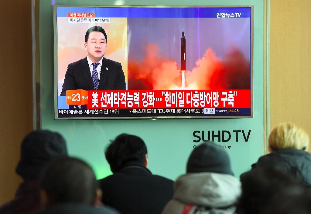 People watch the news showing file footage of a North Korean missile launch at a railway station in Seoul on February 12, 2017 (AFP Photo/JUNG Yeon-Je)