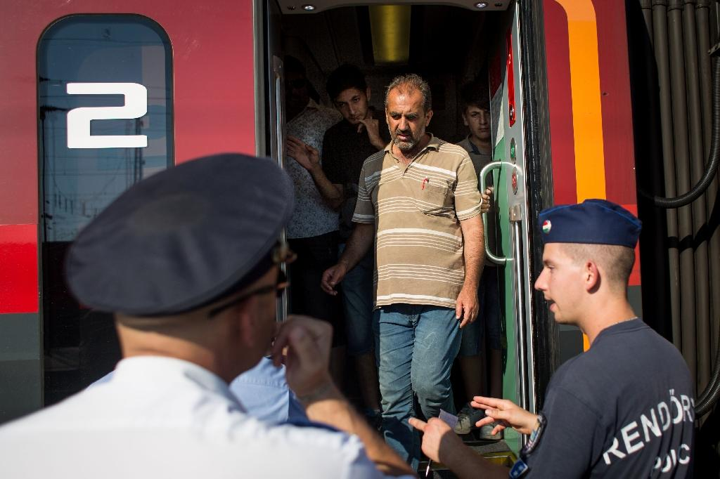 Migrants on the train to Frankfurt / Main undergo a police check at the Austrian - Hungarian border at Hegyeshalom on August 31, 2015 (AFP Photo/Vladimir Simicek)