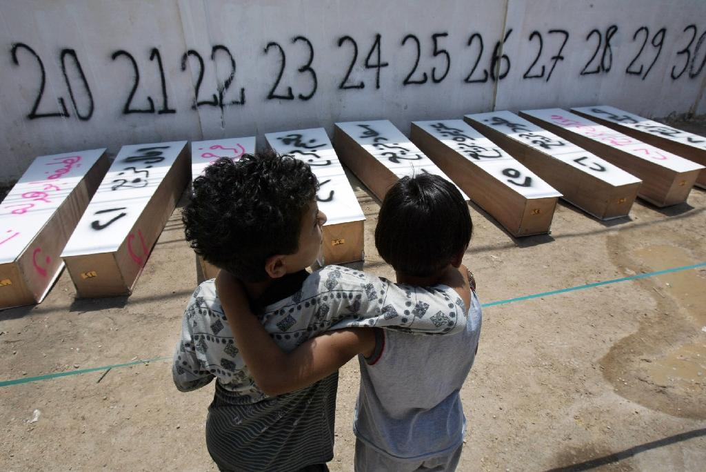 Children stand in front of the coffins of 72 people killed in Israeli air strikes in the southern Lebanese city of Tyre, on July 21, 2006 (AFP Photo/Hassan Ammar)
