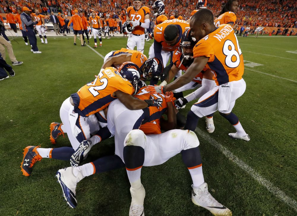 Derek Wolfe (95) hugs Shelby Harris on the bottom of a pile after Harris' game-winning field-goal block. (AP)