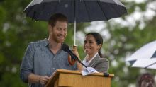 Meghan Markle tries to keep Prince Harry dry in the rain during his heartfelt speech in Dubbo