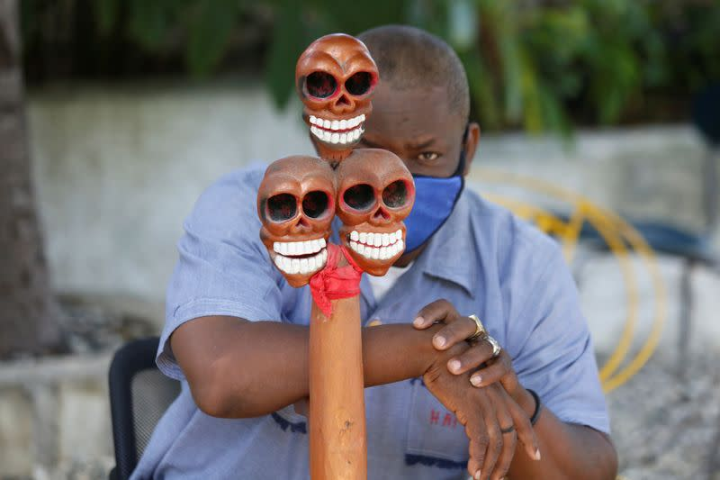 A voodoo priest wearing a face mask to protect from the spread of the coronavirus disease (COVID-19) takes part in a ceremony in Port-au-Prince