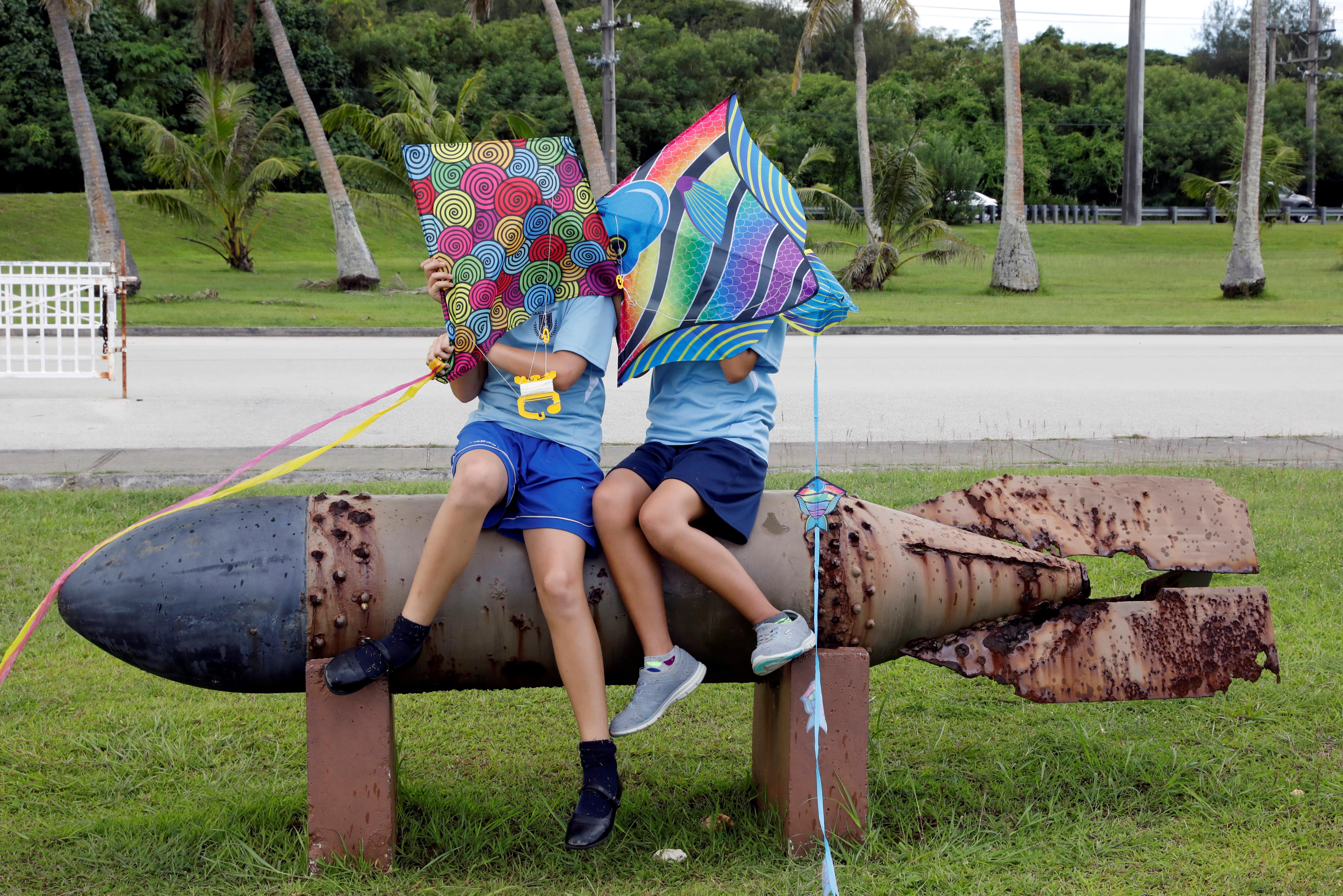 <p>Pupils sit on the World War II remnants of a torpedo at Asan Memorial Park on the island of Guam, a U.S. Pacific Territory, August 11, 2017. (Erik De Castro/Reuters) </p>
