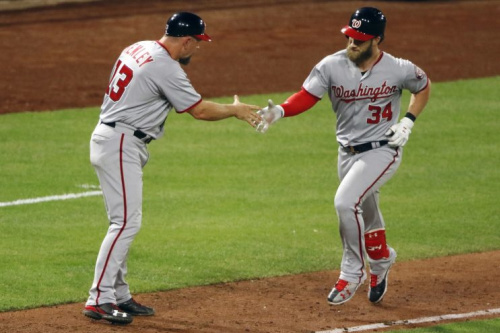 Washington Nationals' Bryce Harper (34) rounds third to greetings from third base coach Bob Henley (13) after hitting a two-run home run off Pittsburgh Pirates relief pitcher Wade LeBlanc in the ninth inning of a baseball game in Pittsburgh, Tuesday, May 16, 2017. The Nationals won 8-4. (AP Photo/Gene J. Puskar)