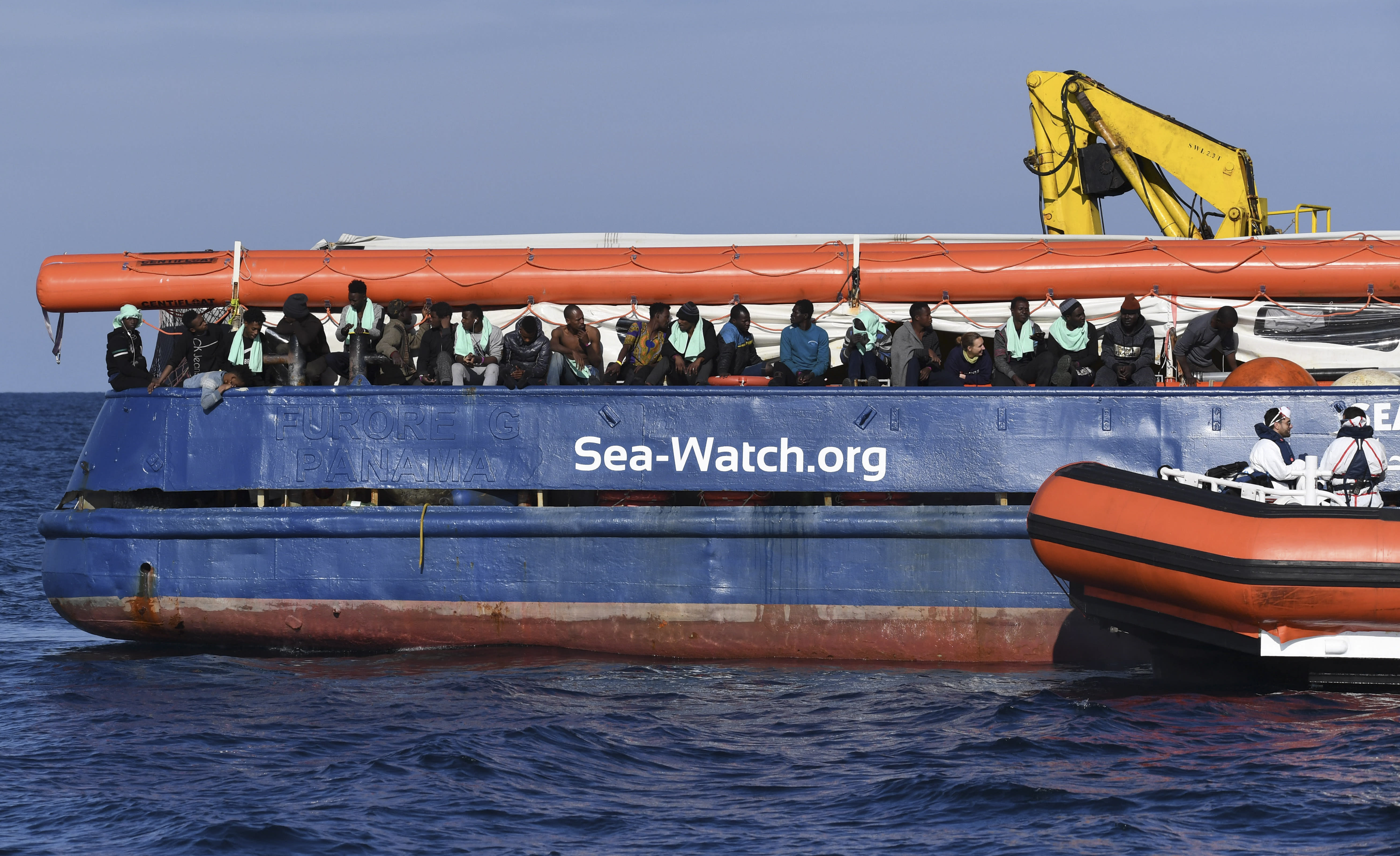 A coastguard boat approaches the German humanitarian group's rescue boat Sea Watch 3, to deliver food and blankets for the cold, off the coast of Syracuse, Italy, Sunday, Jan. 27, 2019. The Italian coast guard is bringing socks, shoes, bread and fruit to 47 migrants who have been stranded at sea for nine days aboard a German ship. (AP Photo/Salvatore Cavalli)